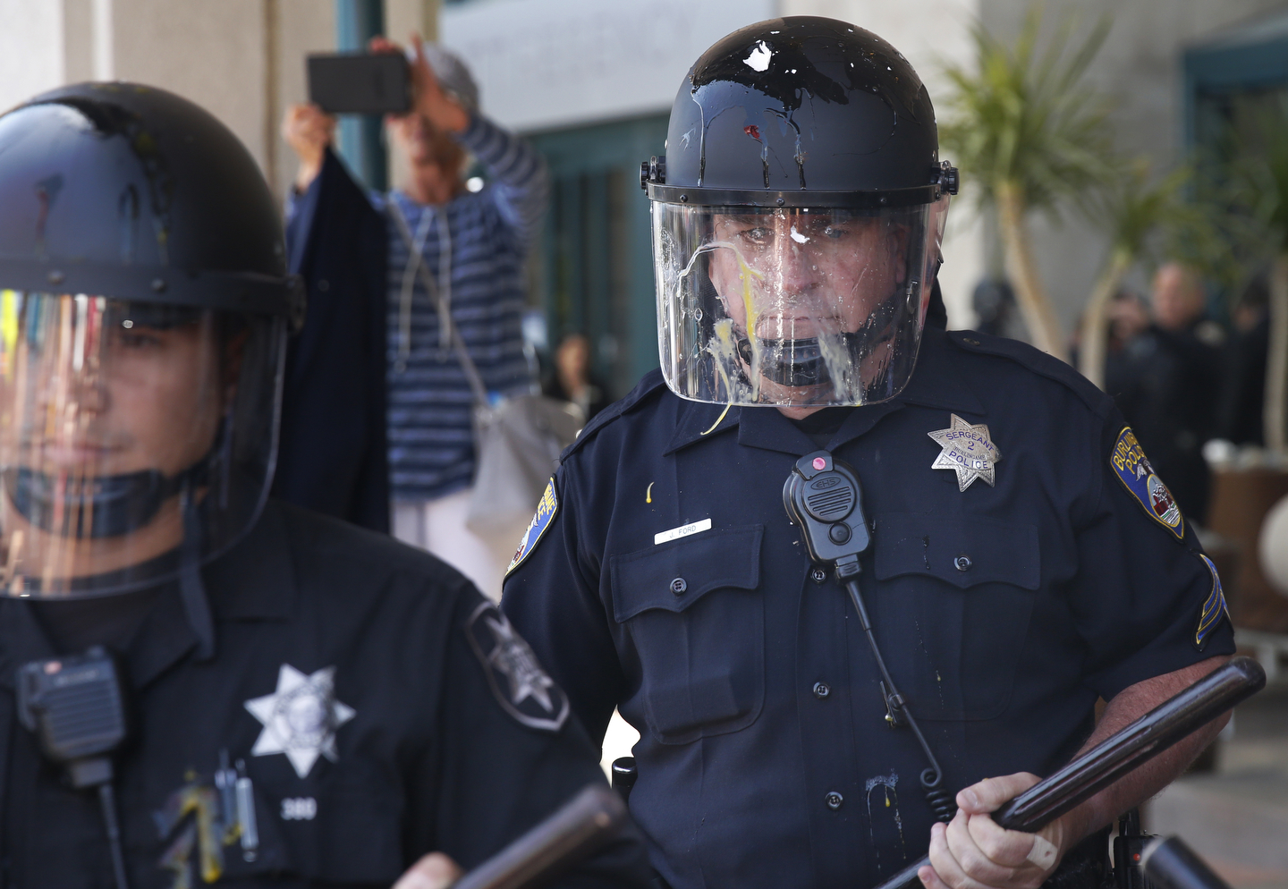 An egg that smashed onto a police officer's face shield runs as he stands between protesters and the front of the Hyatt Regency during the first day of the California Republican Party Convention which featured speeches from Presidential candidates Donald Trump and John Kasich among others April 29, 2016 in Burlingame, Calif.