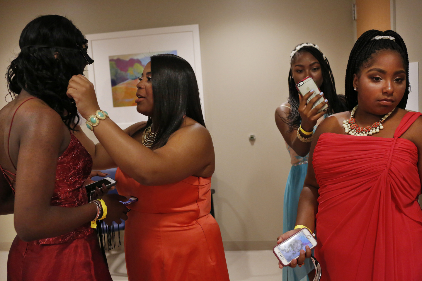 Destiny Willis, 14, left center, adjusts a mask onto Johnae Prowell, 17, far left, as Trinity Hayden, 14, center right, uses her phone and Aarionna Seals, 12, checks out the scene as they wait in the hallway to enter the dance during Kaiser Permanente Oakland's Pediatric Prom at Oakland Medical Center Sept. 24, 2016 in Oakland, Calif. The second annual dance was attended by around 100 teens who were otherwise unable to have the traditional school dance experience due to trauma or illness.
