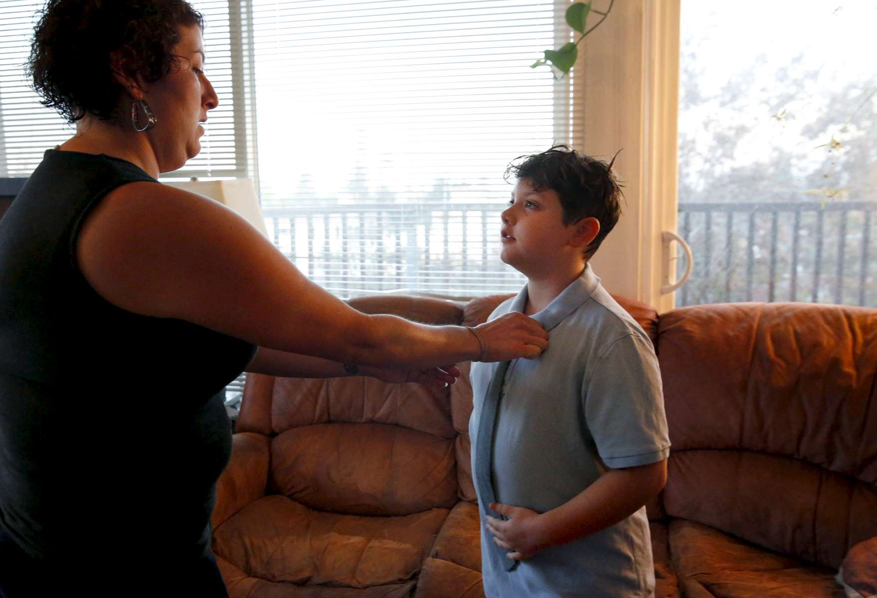 Sara Kaplan helps do her son James', 8, tie as he gets ready for his first day of school August 30, 2016 in Berkeley, Calif. James originally wanted to wear a suit on his first day but his parents talked him down to a polo shirt and tie.