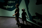 James Kaplan, 8, and his sibling Charley Kaplan, 4, wander through an aquarium during a family outing to Six Flags amusement park Aug. 20, 2016 in Vallejo, Calif.