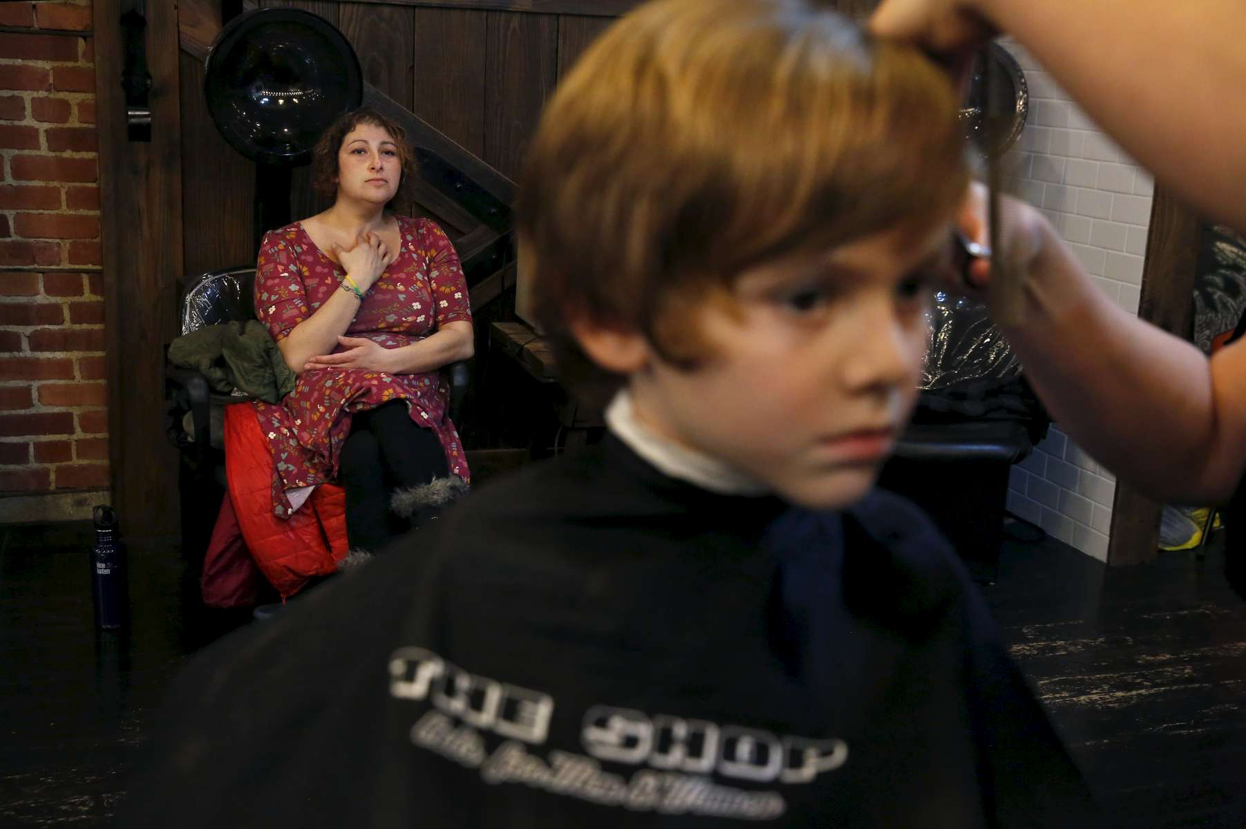 Olivia Kaplan, 4, gets her bangs trimmed by Bobby Jean Larrañaga while her mother Sara watches nervously at The Shop Feb. 17, 2017 in Berkeley, Calif. Olivia, James' sibling, had been describing herself as trans for much of the past year since her brother came out as a transgender boy. Sara and Ben decided to brush it off to see if it was just something she was saying to copy her sibling. But it became apparent over time that it was very real to Olivia. She has always been a feminine child and she finally shouted at her parents that she was a girl at the beginning of the year. They cautiously allowed her to begin the transition. As of June, 2017, Olivia is still happily presenting as a girl. Sara and Ben plan on doing what they have for James: provide a supportive space for their children to be themselves whoever they turn out to be later in life.