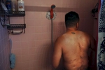 Deep scars from Guillermo's yearslong struggle with Valley Fever can be seen on his back where the disease tried to kill him from inside of his spine as he takes a shower with a temporary, battery powered shower head in his home in Fresno. The poor air quality and increase of dust and air particles has caused an increase in diseases such as Valley Fever. Guillermo purchased the shower head pump to make taking showers with buckets of water easier for him and his mother since their well went dry.
