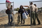 "Maricela Montejano, 49, center, and Gerardo ""Gerry{quote} Anzorena, both residents of the shantytown, clutch their belongings as they are directed by Fresno County Sheriff's officers out of a temporary fence line surrounding the encampment during the eviction."