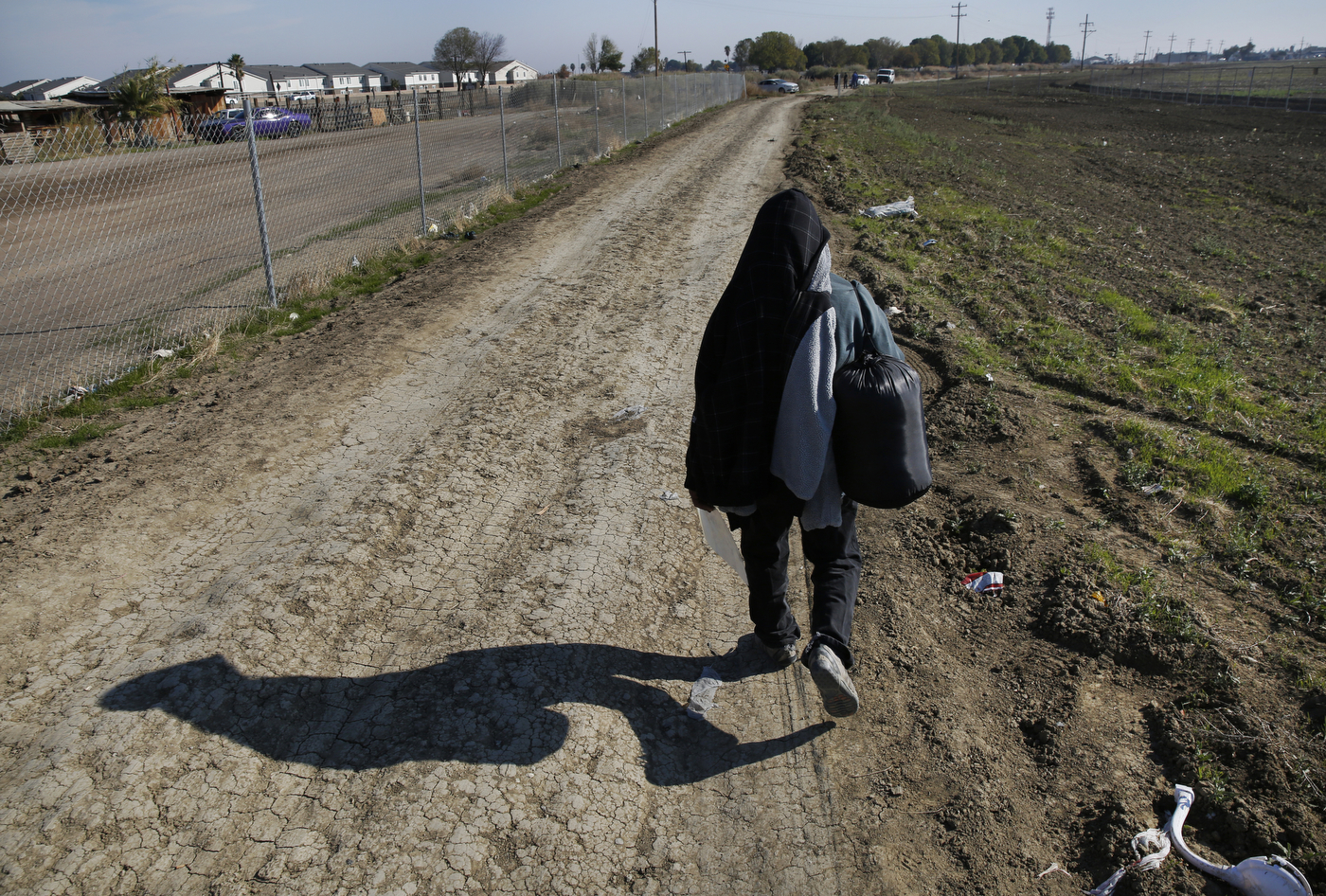 Mena walks down a road away from his home and the shantytown with a few belongings thirty minutes before police are expected to show up to evict him and the other residents. Mena ended up staying with his nephew in Mendota, trying to get work trimming trees in nearby pistachio orchards.