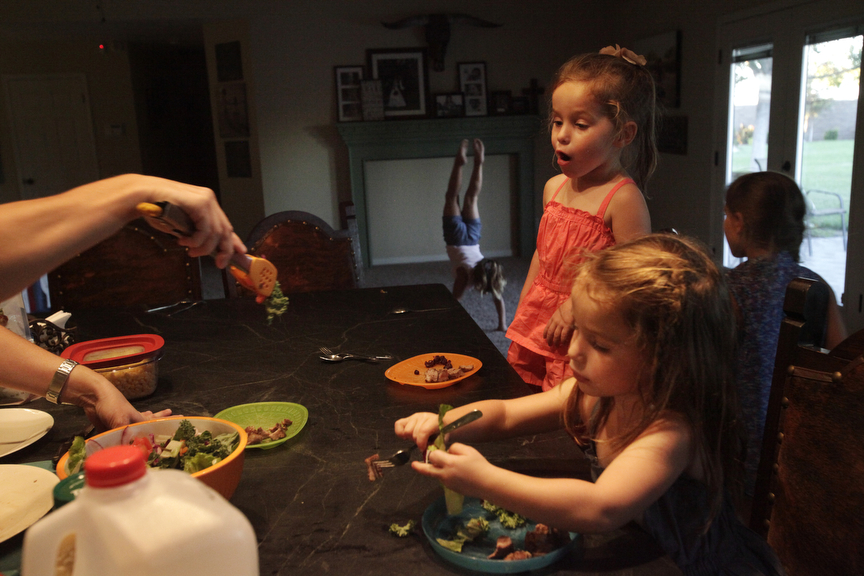 "Darcy Vlot, 35, left, serves salad to her daughters Kasey, 3, left, and Carsyn, 3, as her two other daughters Rylee, 6, back left, and Makenna, 8, back right, play around in their home July 23, 2014 in Chowchilla, Calif. Most Central Valley farmers received no more than a 5 percent water allotment this season from government water sources, leaving many farmers with no choice but to pump ground water to keep their businesses afloat. The practice of pumping ground water is not new, says Case Vlot, 43, a dairy farmer who started Vlot Brother's Dairy and Calf Ranch with his brother from nothing in the 90's in Chowchilla. The difference, he says, is that today the population has increased significantly and {quote}water storage is the same as it was in the 1960's."" Locals have discovered the ground in the area is sinking, due to excessive groundwater pumping."