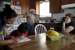 Both unemployed, Jose Pineda Rivas, 61, center, stands in the kitchen with his wife, Maria Callejas, 43, right, as Ruth Fuentes, 32, left, helps her son Jose, 6, with his homework at Fuentes' home April 10, 2014 in Mendota, Calif. Rivas and his wife have been living with the Fuentes' family for four years. Rivas came to the United States in 1988 and was joined by his wife 3 years ago. They left five children behind in El Salvador, who they send money to every month. Both Rivas and his wife work in the fields for their income. Right now neither of them have been able to find steady work and the stress is taking its toll. Rivas has been having trouble sleeping and eating due to a constantly upset stomach and a toothache he cannot afford to repair.