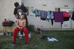 Abraham Tamayo, 12, gets his hair cut by Moises Tamayo, 20, outside of an apartment complex April 14, 2012 on the edge of town in Mendota, Calif.
