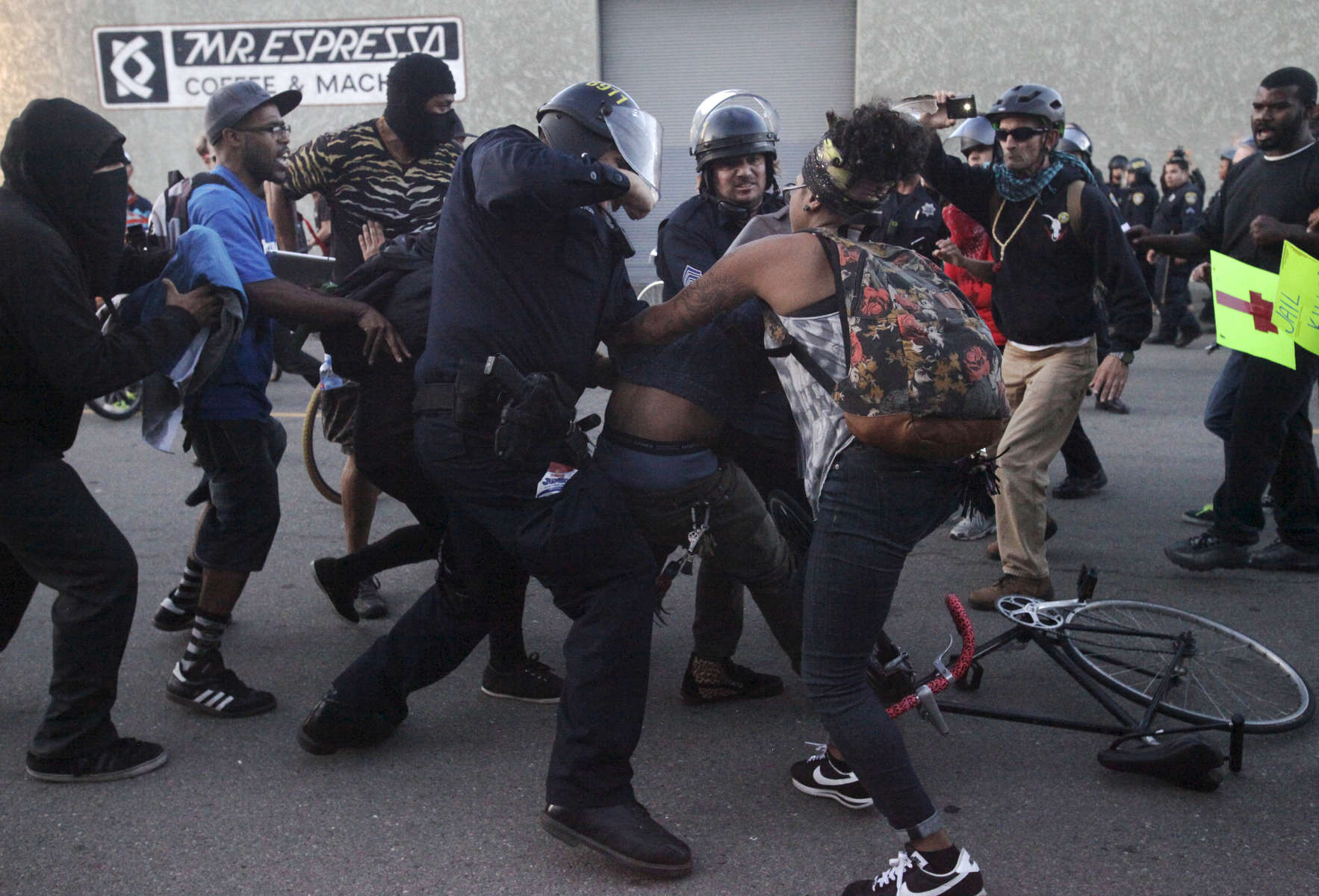 A woman tries to pull a protester from police officers after a scuffle broke out between them during an {quote}F the Police{quote} march held in solidarity with Ferguson, Mo., where there was a fatal shooting of an unarmed 18-year-old black man earlier in the week August 15, 2014 in Oakland, Calif.