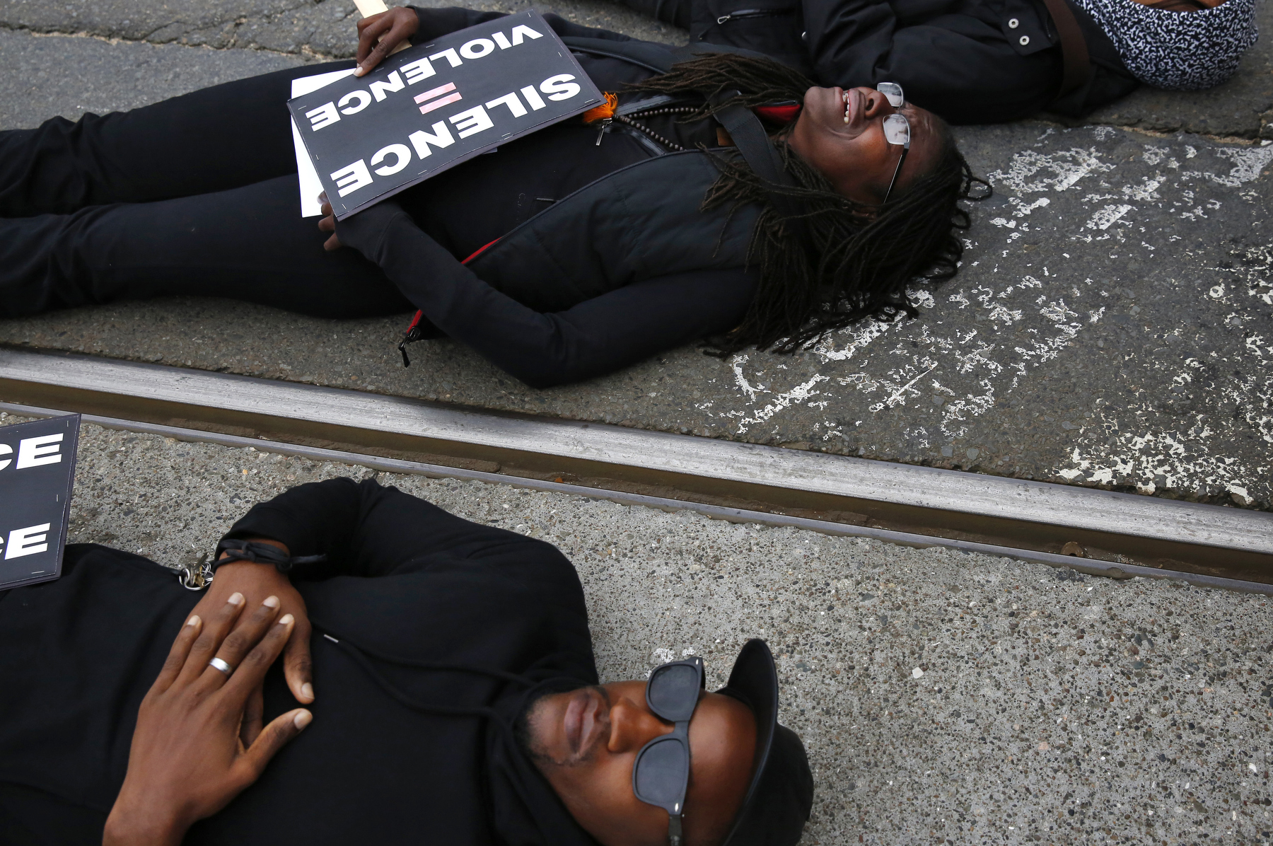 From left, Sampson McCormick, Kin Folkz and Puck Lo lay in the street as they observe four and a half minutes of silence while blocking the 101 south freeway entrance and exit ramps at the intersection of Octavia and Market streets during a {quote}LGBT Rally and March for an End to Police Violence{quote} Dec. 24, 2014 in San Francisco, Calif.