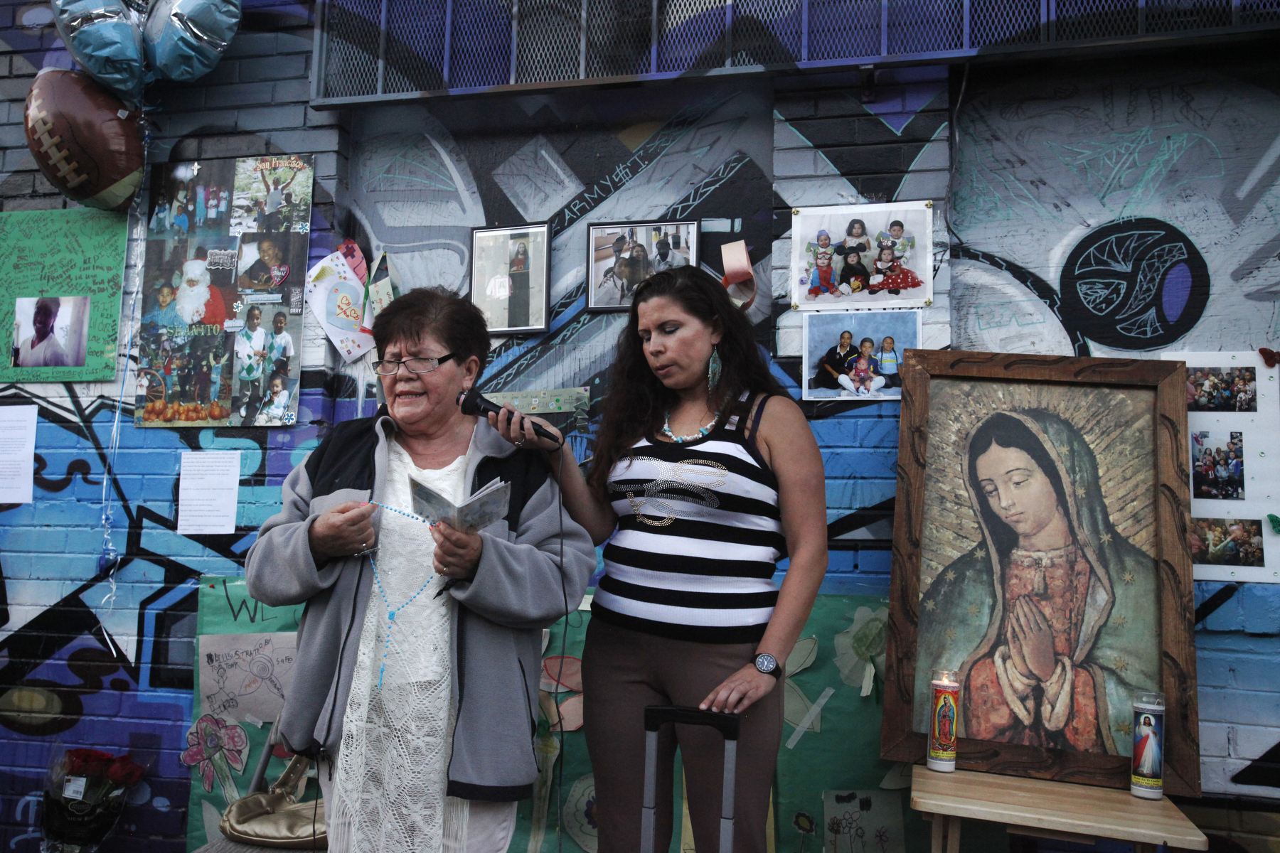 Victoria Morales, left, the grandmother of Williams, and his Aunt Ruth Morales lead the rosary during a vigil held in honor of Rashawn Williams, 14, at the corner where he was stabbed to death the previous week on 26th and Folsom Sept. 7, 2014 in San Francisco, Calif.