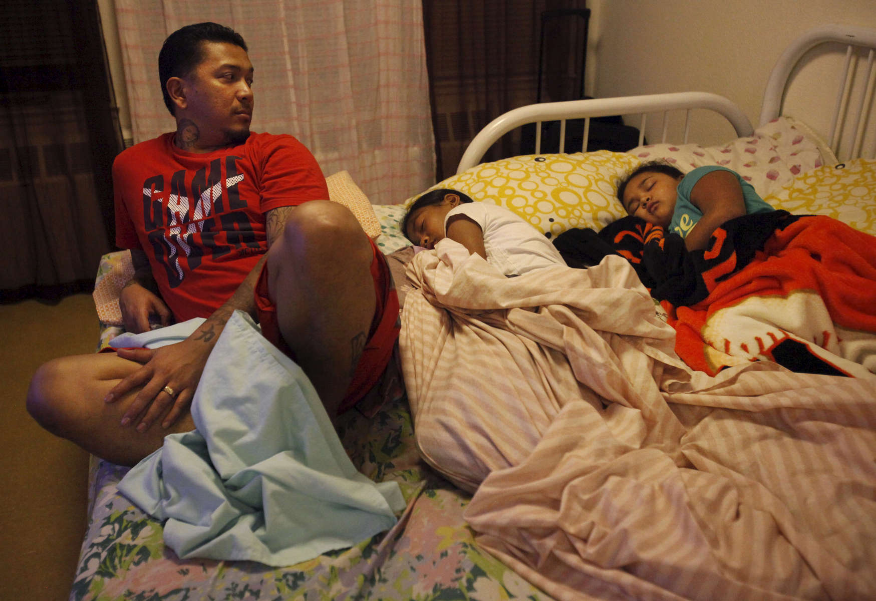 Red Rodrigo glances over at his two daughters, Brennelyn, 8, right, and Bryanna, 11, as they sleep in the bed he and his wife (their mother) sleep on in the living room in their transitional apartment Oct. 21, 2014 in San Francisco, Calif. Because the children grew up sleeping together, sometimes all five in one bed, the two youngest still like sleeping with their parents. The Rodrigo family has been living in transitional housing for almost a year after staying with a large number of family members in a very small apartment. The family hasn\'t really had a place of their own and have enjoyed having the apartment to themselves but their time allotted in the place is almost up.