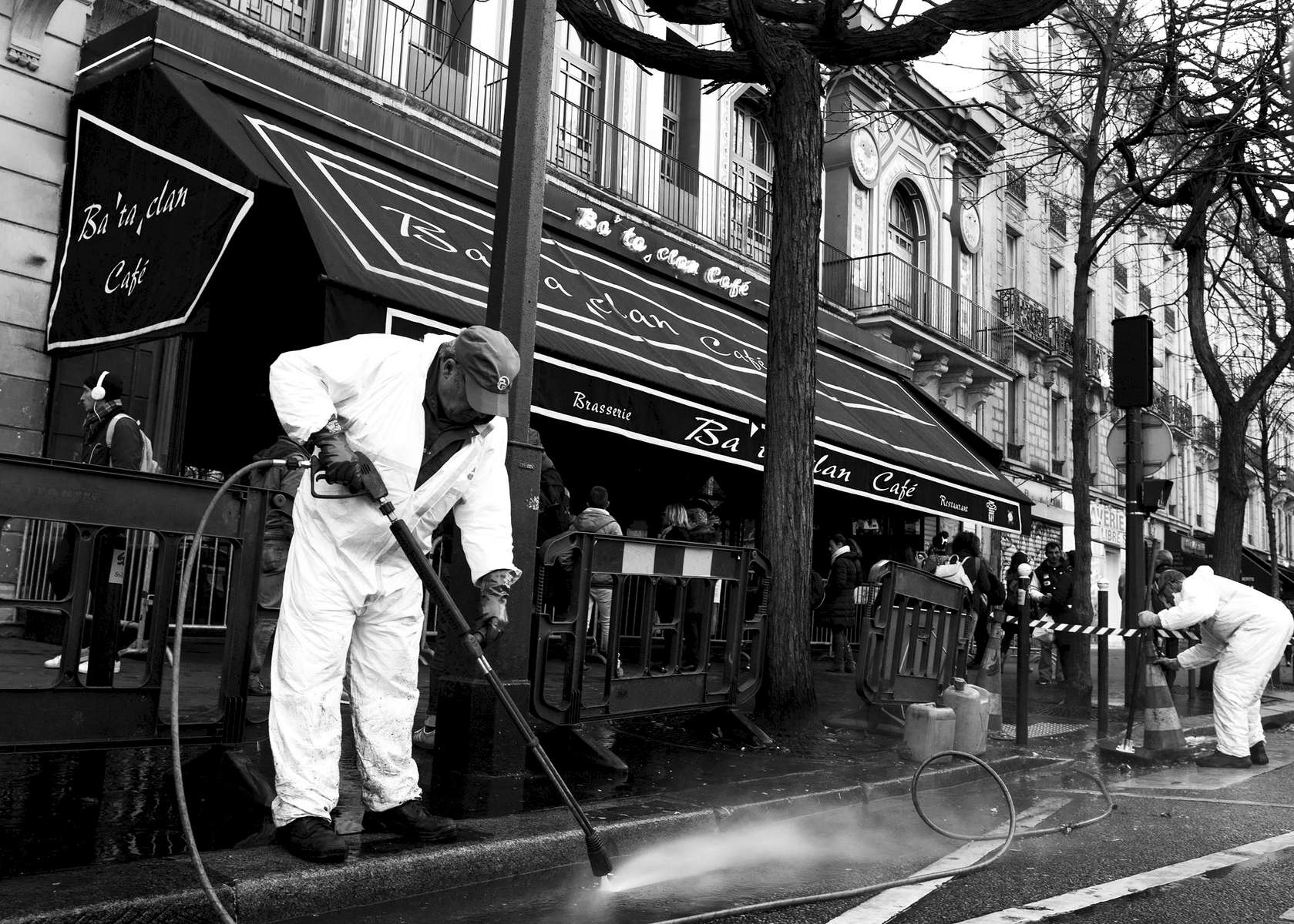 Employees of Property of Paris clean the sidewalk in front of the Bataclan, after the makeshift memorial that was created after the attacks was removed across the street, on December 22, 2015, Paris, France.  90 persons were killed  during a concert, during the November 13 attacks. Hundreds of people come everyday to reflect at this makeshift memorial as well as the ones that were created on the locations of the attacks.
