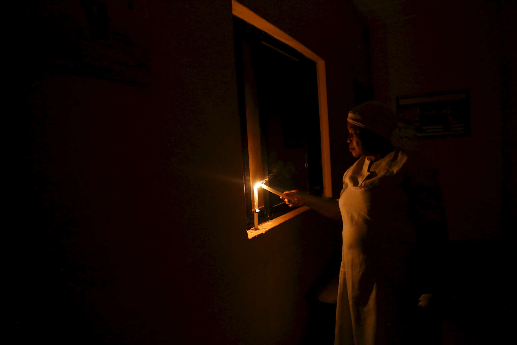 Nurse Williams light a candle at night during a power outage at the medical facility of Kuchigoro in Abuja, Nigeria.
