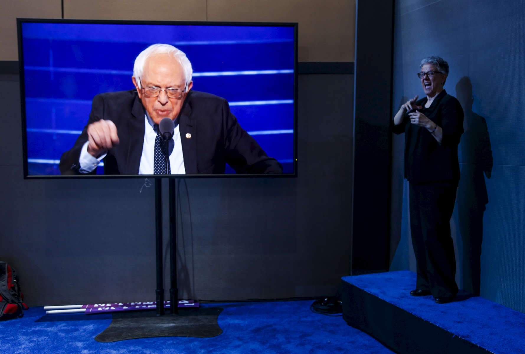 Senator Bernie Sanders (I-VT) address the delegates, seen on a TV screen, while woman translates the speech for non-hearing people, on the first day of the Democratic National Convention.