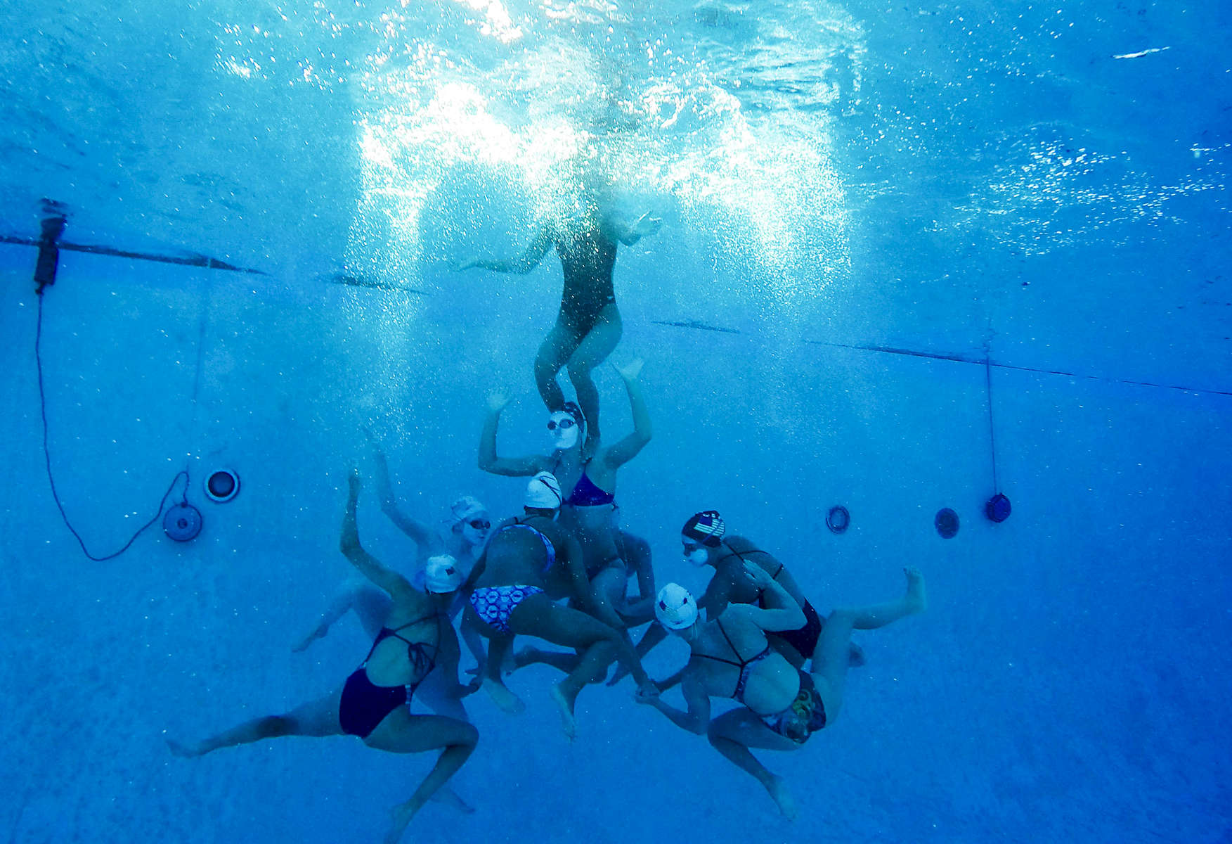 The US junior synchronized swimming team works on one of their lift where they lift two girls out of the water without touching the ground.