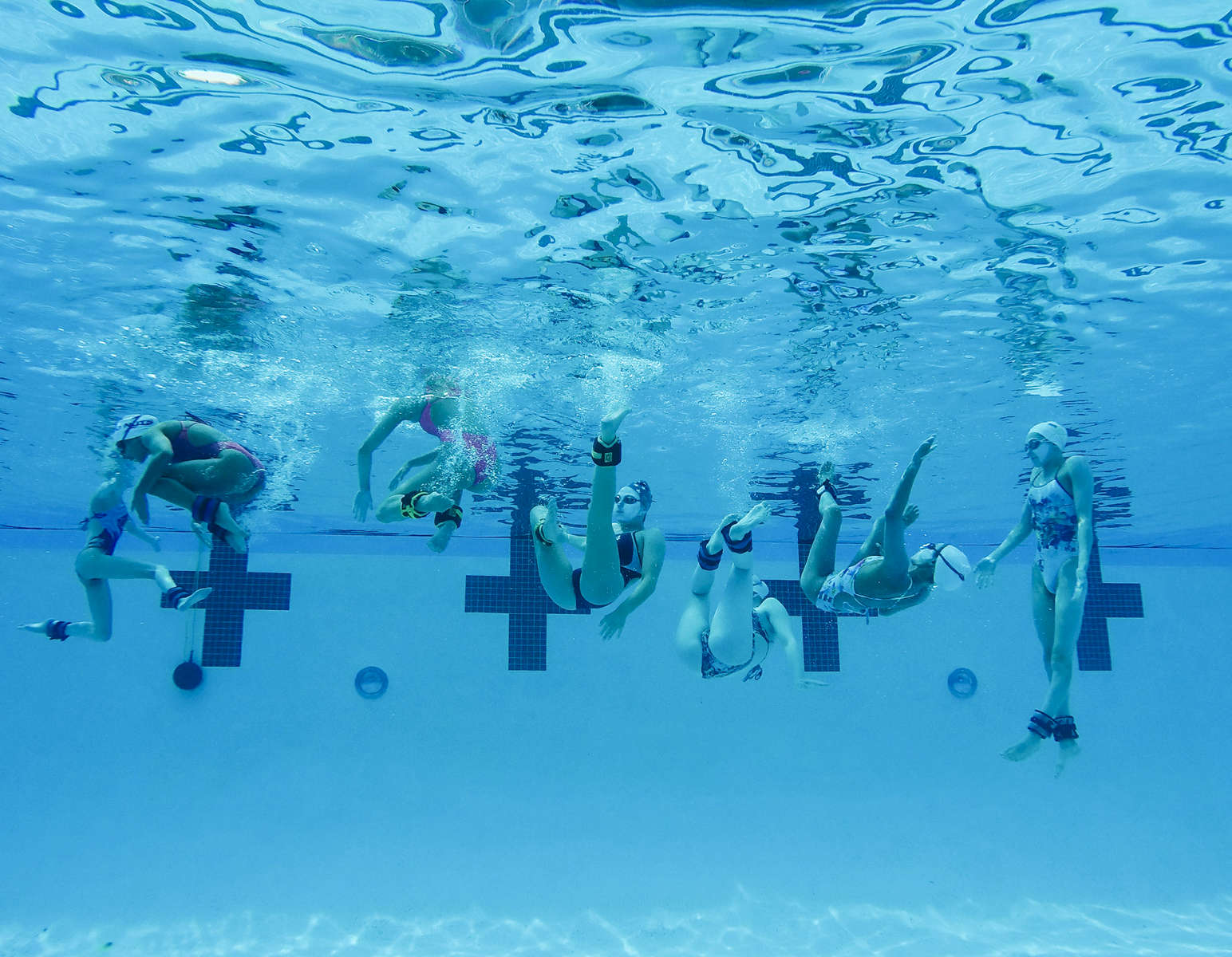 The US junior synchronized swimming team trains with additional weights on their feets.