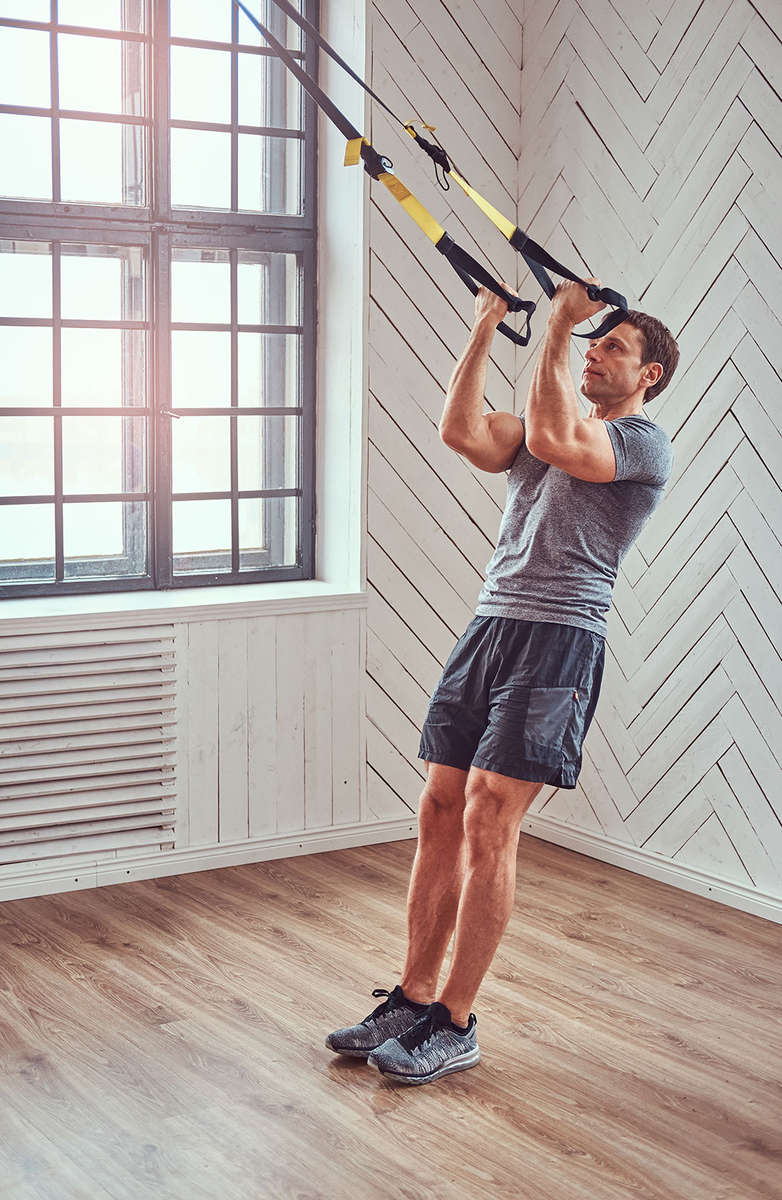 Fit 'N' Well personal training client at working out with a TRX system.